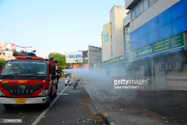 Firefighters from Ahmedabad Fire and Emergency Services spray disinfectant over an ATM of the Corporation Bank on the National Fire Service Day,...