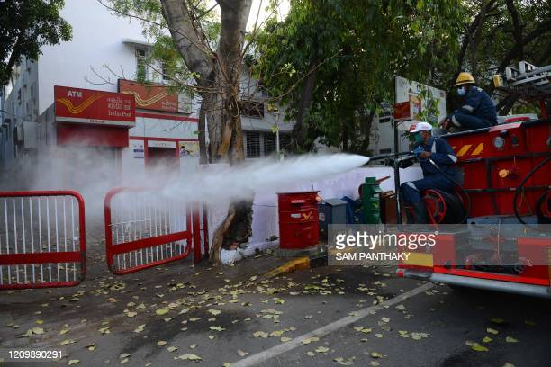 Firefighters from Ahmedabad Fire and Emergency Services spray disinfectant over an Indian Postal Department building on the National Fire Service...