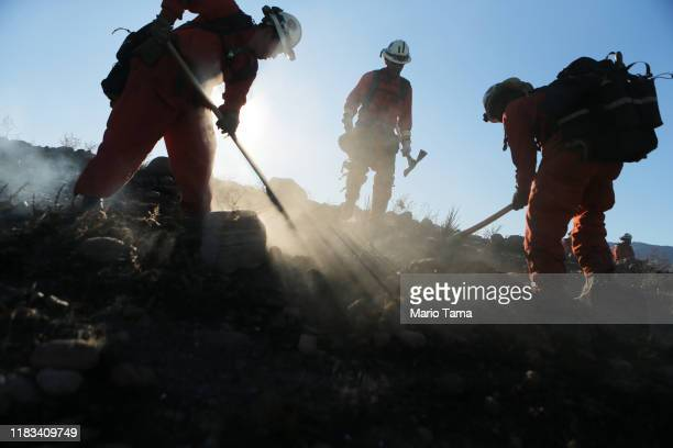 Firefighters from an inmate hand crew work to put out hot spots from the Tick Fire on October 25 2019 in Canyon Country California The fire has...