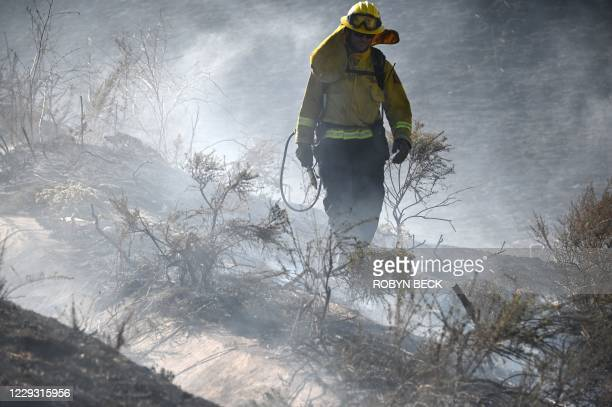 Firefighters from Cal Fire set backfires to prevent wildfire from spreading into a residential area at the Blue Ridge Fire in Chino, California,...