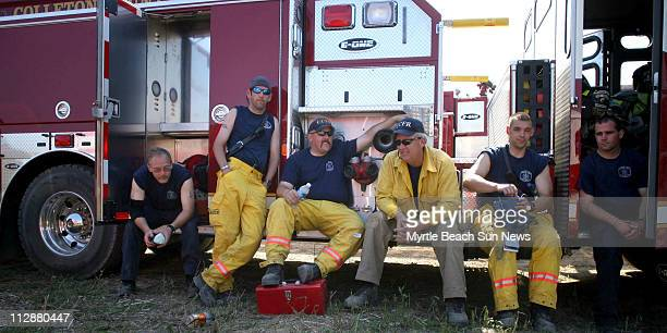Firefighters from Columbus County NC trade off fire stories during a dinner break at the staging area off SC 22 and SC 90 in western Horry County...