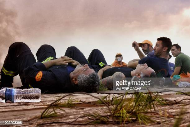 Firefighters from Cyprus rest during a wildfire at the village of Kineta near Athens on July 25 2018 At least 79 people died in huge wildfires around...