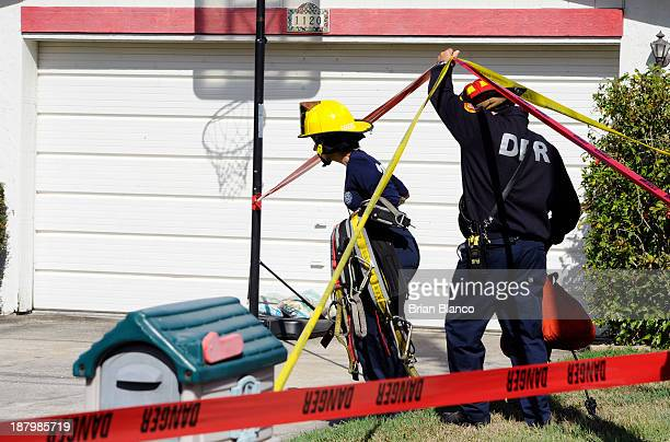 Firefighters from Dunedin Fire Rescue make their way to survey damage to a residential home partially consumed by a sinkhole on November 14 2013 in...