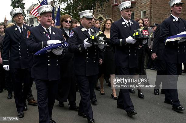 Firefighters from Engine 201 carry flags and helmets as they lead the procession during a memorial service for Christopher Pickford at the Episcopal...