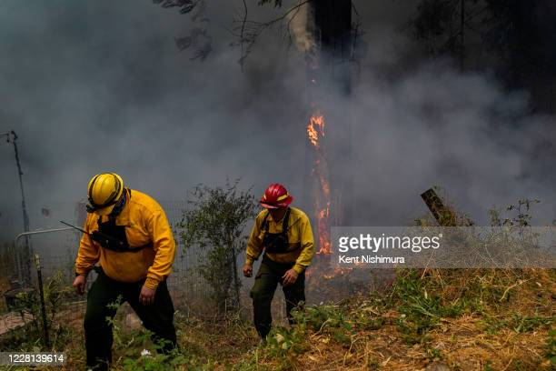 Firefighters from First Strike Engine 1 out of Eugene, Oregon inspect a fire burning near a structure along Pine Flat road during the CZU August...