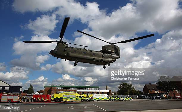 Firefighters from Merseyside Fire Brigade look on as an RAF Chinook helicopter lands rescue crews during the UK's biggest ever rescue exercise on...