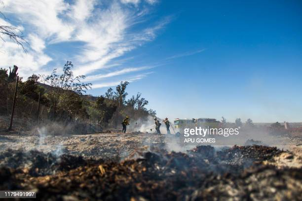 Firefighters from Santa Fe Springs battle to control hotspots of the Maria Fire in Santa Paula Ventura County California on November 02 2019 The...