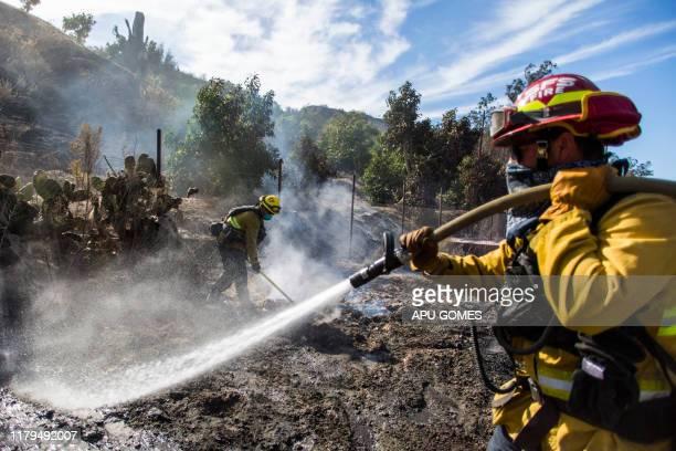 Firefighters from Santa Fe Springs battle to control hotspots of the Maria Fire in Santa Paula Ventura County California on November 02 2019 The...