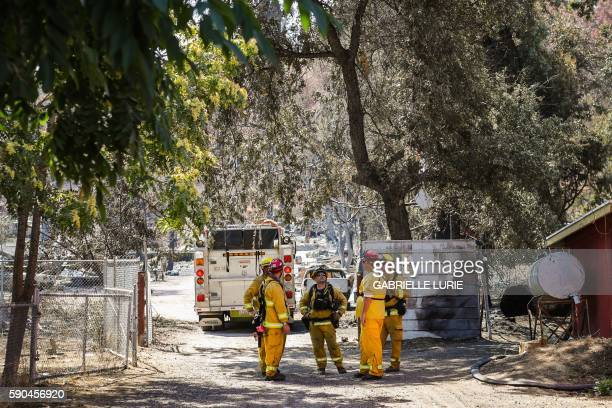 Firefighters gather as they help with the destruction caused by the Clayton Fire in Lower Lake California August 16 2016 A man was arrested and...