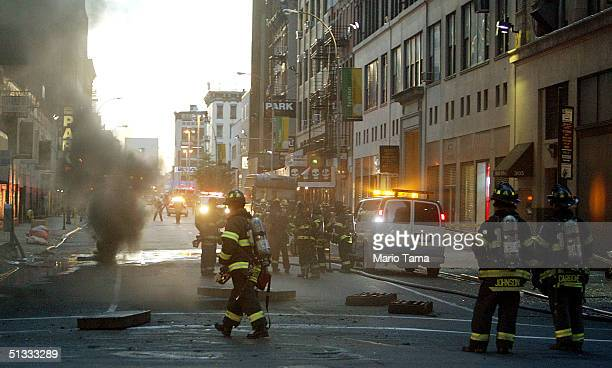 Firefighters gather at the scene of an underground blaze following an explosion near Eighth Avenue and 38th Street during the evening rush hour...