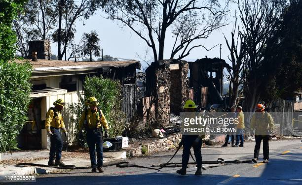 Firefighters gather their hoses near destroyed homes along North Tigertail Road near the Getty Center in Los Angeles California on October 29 2019...