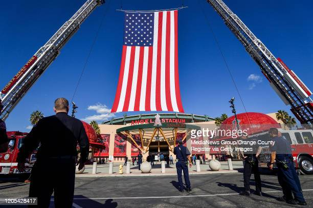Firefighters hang a giant flag outside Angel Stadium before the start of a memorial service for the Altobelli family in Anaheim CA on Monday Feb 10...