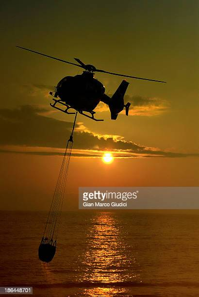 CONTENT] Firefighters helicopter in action at sunset in Civitavecchia bay
