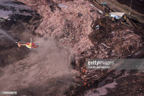 A firefighters' helicopter overflies the area as rescuers work in the search for victims after the collapse of a dam which belonged to Brazil's giant...
