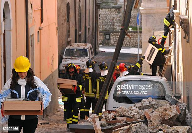 Firefighters help victims of the April 6 earthquake to recover their personal belongings from their houses, in L 'Aquila, on April 13, 2009. The...