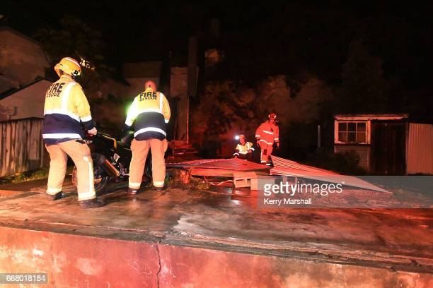 Firefighters help with cleaning up after high winds from Cyclone Cook blow down a shed in Battery Road on April 13 2017 in Napier New Zealand Heavy...