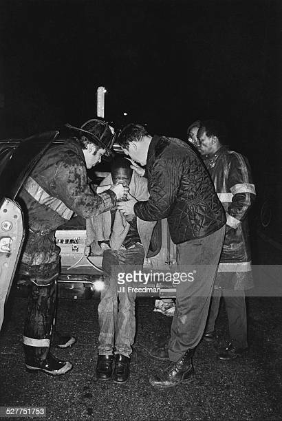 Firefighters helping a boy breathe with an oxygen mask USA circa 1980