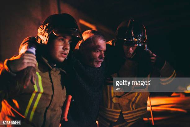 firefighters helping a man - burn injury stock photos and pictures