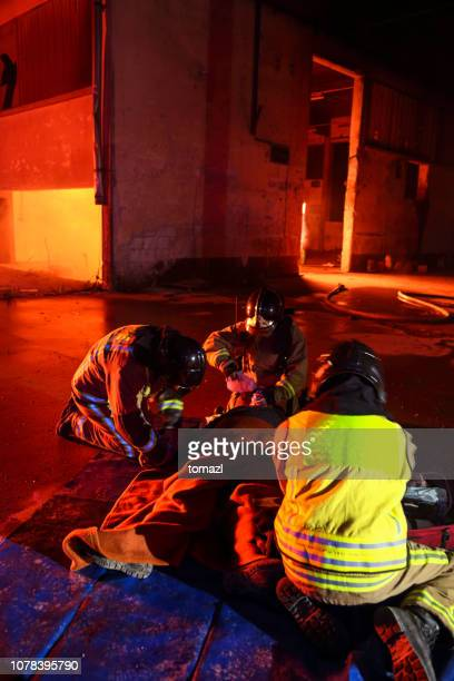 firefighters helping an injured man - fire protection suit stock photos and pictures
