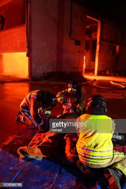 bombeiros ajudando um homem ferido - fire protection suit - fotografias e filmes do acervo