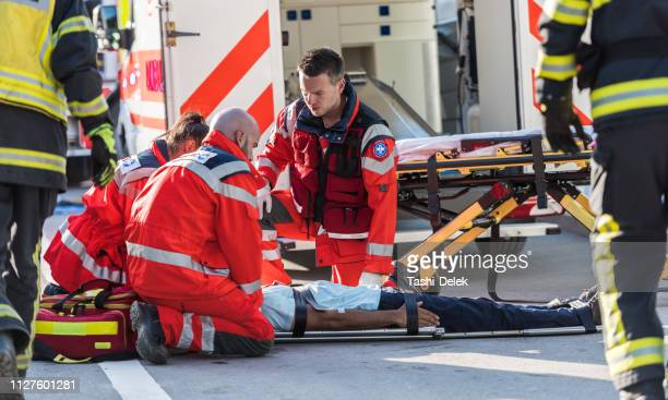 firefighters helping rescue team - paramedic stock pictures, royalty-free photos & images