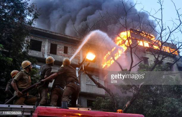 Firefighters hold a hosepipe to douse flames as a fire has broken out in a multistorey commercial building at Chandni Chowk in Kolkata on June 16 2019