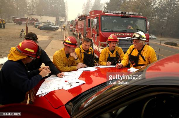 Firefighters hold a morning meeting as they continue to battle the Camp Fire on November 10 2018 in Paradise California Fueled by high winds and low...
