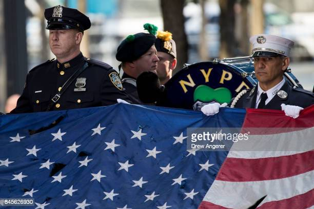 Firefighters hold up a flag that flew at the World Trade Center at the start of a commemoration ceremony for the victims of the September 11...