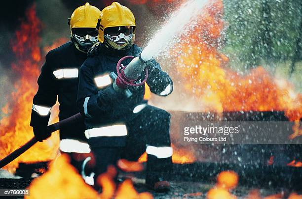 firefighters holding a hose and spraying water - fire protection suit stock photos and pictures