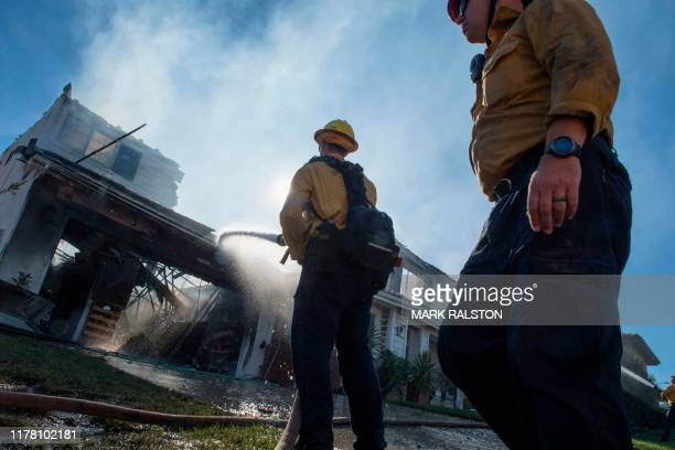 Firefighters hose down a burning house during the Tick Fire in Agua Dulce near Santa Clarita California on October 25 2019 California firefighters...