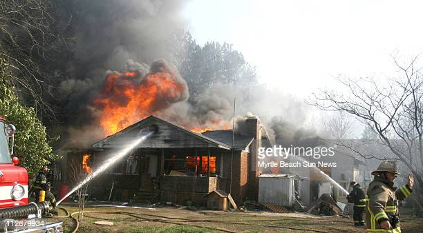 Firefighters hose down Donald Paul's home in western Horry County near Conway South Carolina on Sunday February 10 2008