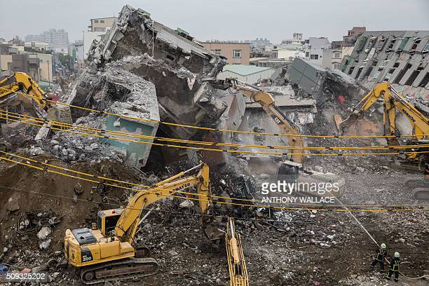 TOPSHOT Firefighters hose down falling rubble to prevent dust from rising as excavators are used during the search and rescue operation at the...