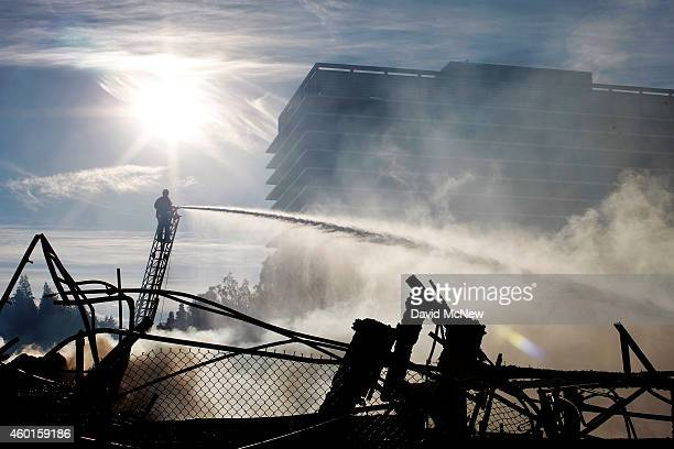 Firefighters hose down the smoldering ruins of a seven-story apartment building under construction alongside the 110 freeway that was destroy in an...