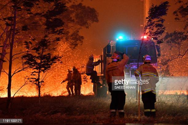 Firefighters hose down trees as they battle against bushfires around the town of Nowra in the Australian state of New South Wales on December 31 2019...