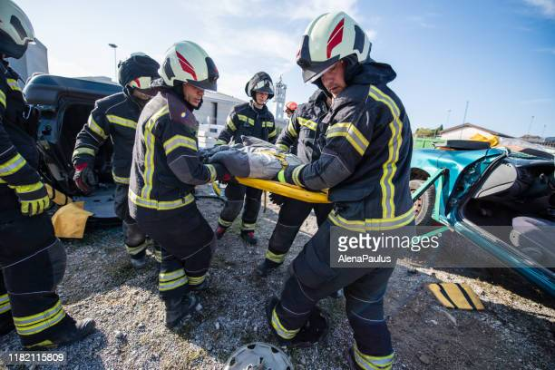 firefighters in a rescue action in a car accident bearing the victim - rescue stock pictures, royalty-free photos & images
