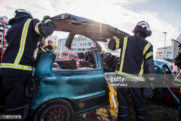 firefighters in a rescue action in a car accident - rescue worker stock pictures, royalty-free photos & images