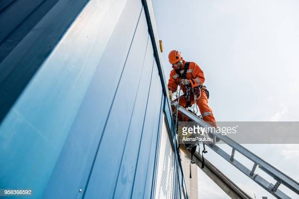 firefighters in a rescue operation - accident on the roof - sicurezza foto e immagini stock