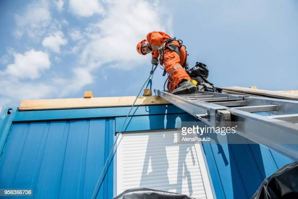 firefighters in a rescue operation - accident on the roof - high up stock photos and pictures