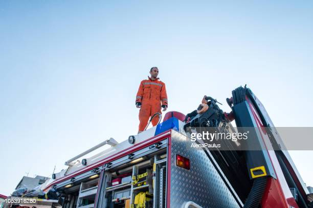 firefighters in a rescue operation - standing on the fire truck - rescue worker stock pictures, royalty-free photos & images