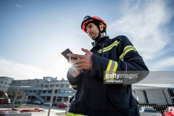 firefighters in a rescue operation training, man using a smart phone - firefighter stock pictures, royalty-free photos & images