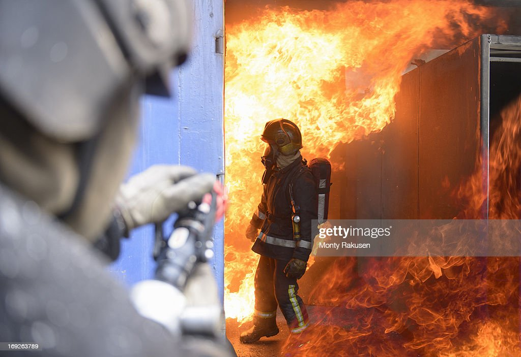 Firefighters in fire simulation training facility : Stock Photo