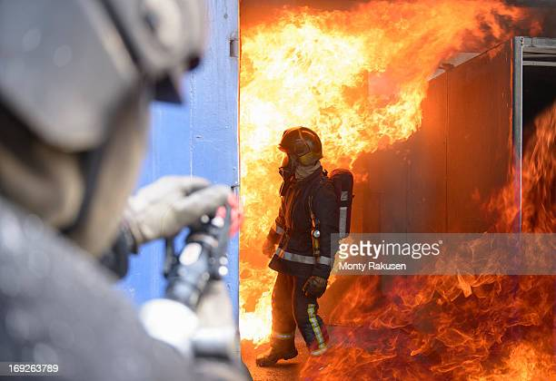 Firefighters in fire simulation training facility
