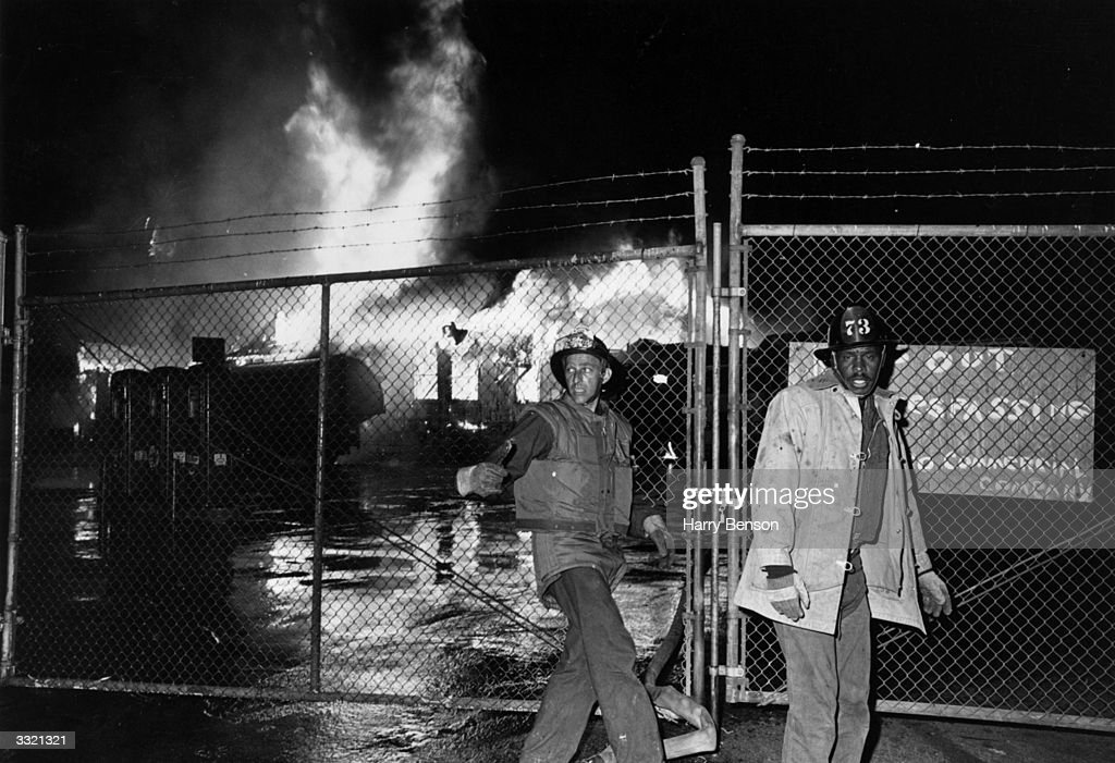 Fire-fighters in front of a blazing building during the Watts Riots in Los Angeles, California, 11th-15th August 1965.