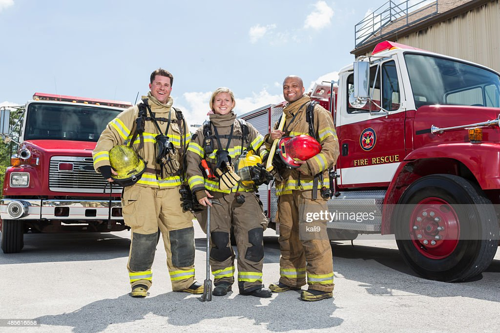 Firefighters in protective gear with fire rescue trucks : Stock Photo