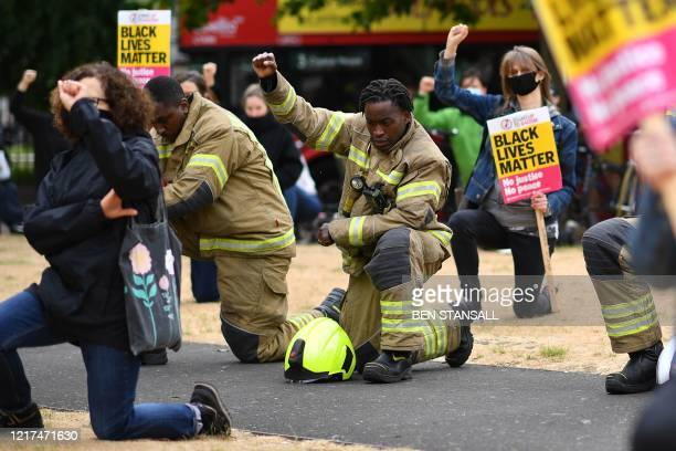 Firefighters in uniform gather with people as they kneel during an antiracism demonstration in Windrush Square Brixton in south London on June 3...