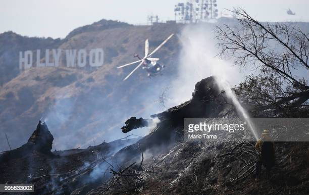 Firefighters including a helicopter work the Griffith fire at Griffith Park near the historic Griffith Observatory and the iconic Hollywood sign on...
