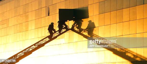 TOPSHOT Firefighters inspect a wall of the Rio shopping mall in Moscow on July 10 2017 Ten people poisoned by smoke were hospitalised after a fire...