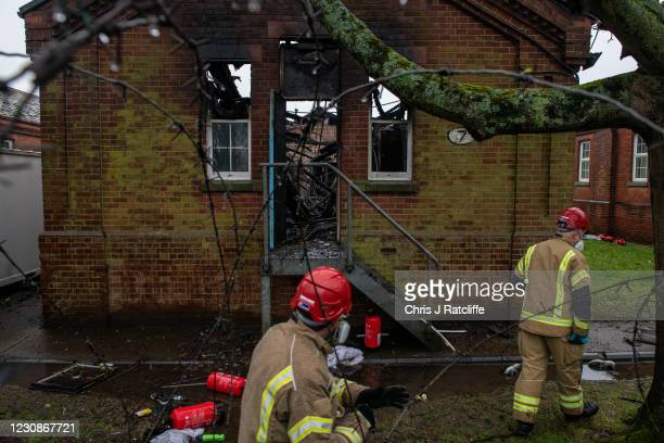 Firefighters inspect the charred remains of a block at Napier Barracks after police have said a fire was started deliberately, on January 30, 2021 in...