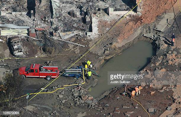 Firefighters investigate a massive crater at the scene of a gas main explosion September 10 2010 in San Bruno California Thirty eight homes were...