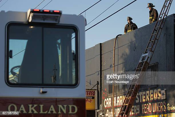 Firefighters investigate the scene of a overnight fire that claimed the lives of at least nine people at a warehouse in the Fruitvale neighborhood on...